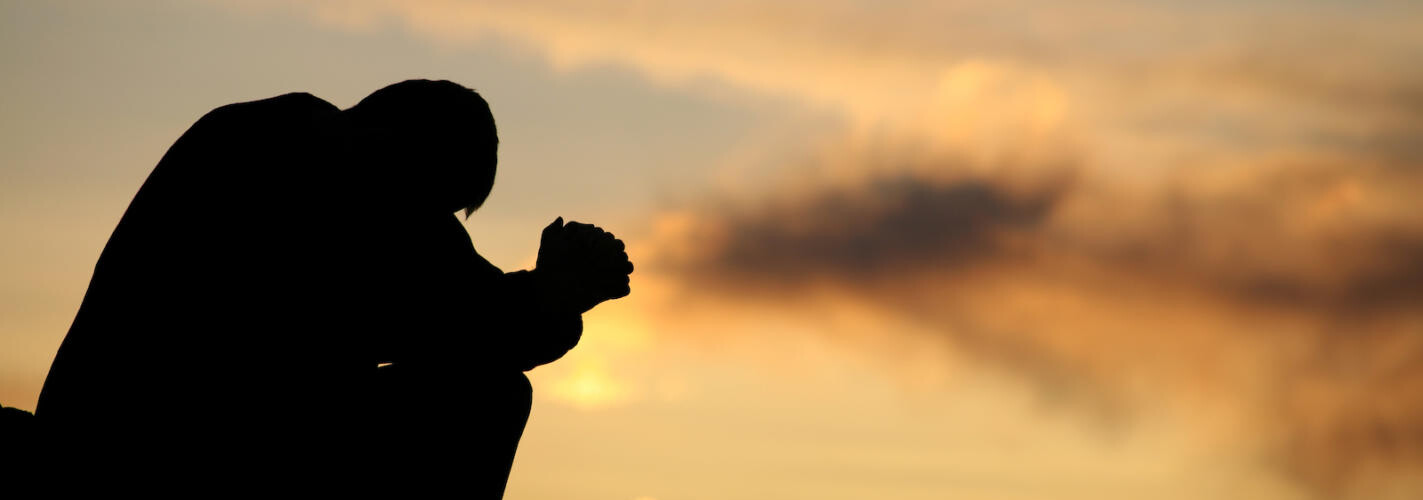 Silhouette of Unrecognizable Man Praying Outside