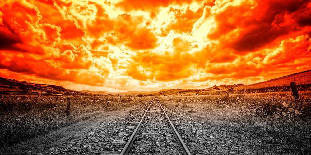 railroad tracks with burring sky
